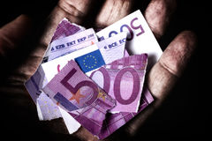 Mãos sujas que guardam umas cinco cem cédulas quebrada dos euro Imagem de Stock