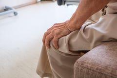 Mãos superiores velhas que aferram-se a seu joelho foto de stock