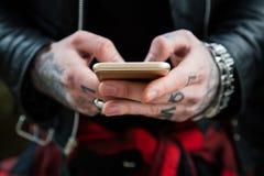 Mãos Tattooed do homem com smartphone Foto de Stock Royalty Free