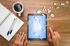 Mãos usando o tablet pc com mapa do mundo, ícones do social e do negócio, caderno, penas e copo de café quente na mesa de madeira Fotografia de Stock