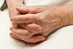 Mãos velhas clasped em joelhos Imagem de Stock