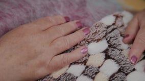 Mãos velhas de uma mulher idosa que encontra-se no sofá na cosmetologia vídeos de arquivo