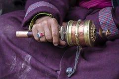 Mãos velhas de uma mulher tibetana que guarda a roda budista em um monastério de Hemis, distrito da oração de Leh, Ladakh, Jammu  imagens de stock