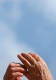Mãos velhas em um céu para trás Fotos de Stock