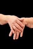 Mãos velhas enrugadas no fundo preto Fotografia de Stock Royalty Free