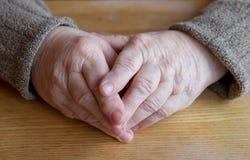 Mãos velhas fêmeas na tabela Fotos de Stock Royalty Free