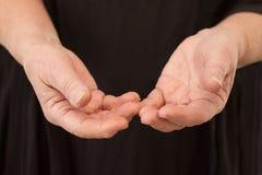 Mãos velhas - mãos humanas no fundo preto Fotografia de Stock Royalty Free