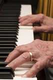Mãos velhas no piano Fotos de Stock Royalty Free