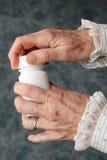 Mãos velhas que abrem o frasco de comprimido Foto de Stock Royalty Free