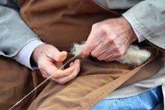 Mãos velhas que giram as lãs Fotografia de Stock