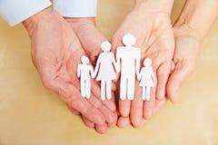 Mãos velhas que guardam a família de papel Imagens de Stock