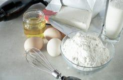Mąka i cukier w szklanym zbiorniku, jajkach i maśle na stole, zdjęcie stock