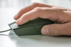 Mężczyźni wręczają na komputerowej myszy z białym biurkiem w tle zdjęcia royalty free