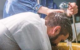 Mężczyzna brodaty klient modnisia zakład fryzjerski Mężczyzna z brodą i wąsy z ręcznikiem na ramionach, samiec ręki z prysznic da zdjęcie stock