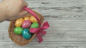 Mężczyzna czyści prezenta kosz z kolorowymi Wielkanocnymi jajkami od drewnianego stołu, kopii przestrzeń, dekoracja zdjęcie wideo