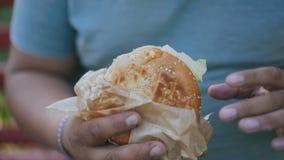 Mężczyzna plenerowy cieszy się jego świeżego hamburger Niezdrowy jedzenie i nadwaga zagrożenia zagrożenie zbiory wideo