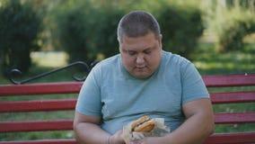 Mężczyzna plenerowy odpakowywa jego hamburger Niezdrowy jedzenie i nadwaga zagrożenia zagrożenie zbiory