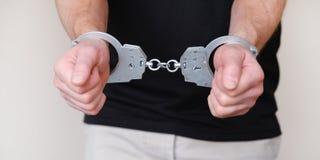 Mężczyzna przy komendą policji Kajdanki na nadgarstkach zatrzymujący mężczyzna obrazy royalty free