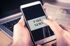 Mężczyzna ` s ręka trzyma smartphone z Sfałszowanymi wiadomości słowami na ekranie Sfałszowana wiadomość, bajerowania pojęcie zdjęcia royalty free