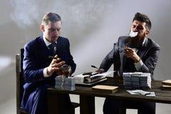 Mężczyzna siedzi przy stołem z stosami pieniądze i maszyna do pisania Firma angażująca w bezprawnym biznesie Biznesmenów dyskutow zdjęcie royalty free