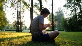 Mężczyzna używa smartphone w parku przy zmierzchem podczas gdy siedzący na trawie zbiory wideo