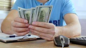Mężczyzna w błękitnej koszulki odliczających dolarach i podsadzkowej podatek formie zbiory wideo