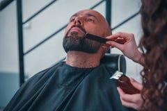 Mężczyzna w fryzjera męskiego sklepie dla fachowej traktowanie brody i włosy fotografia stock