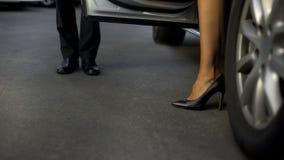 Mężczyzna w kostiumu otwiera samochodowego drzwi dla wysokości heeled żeńskiego szefa, akcydensowi obowiązki, w górę fotografia royalty free