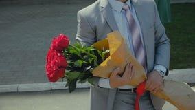 Mężczyzna w kostiumu z bukietem róże, prezent dla rocznicy lub wszystkiego najlepszego z okazji urodzin, zbiory wideo