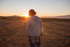Mężczyzna w nieskazitelnym krajobrazie podczas pięknego płonie zmierzchu zdjęcia stock