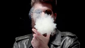 Mężczyzna w skórzanej kurtki i modnisia okularach przeciwsłonecznych zakrywa ramę z bielu dymem zdjęcie wideo