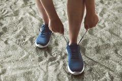 Mężczyzna wiąże działających buty na plaży obraz stock
