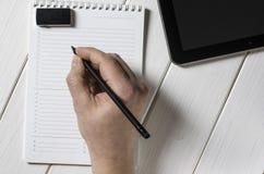 Mężczyzna wręcza pisać notatkach notatnik na drewnianym stole w ministerstwo spraw wewnętrznych zdjęcie stock