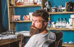 Mężczyzna z brodą i wąsy siedzi w fryzjerach krzesło, piękno dostawy na tle Modniś z brodą czeka zdjęcie royalty free