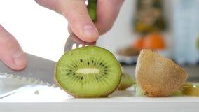 Mężczyzny cięcie z nożem kiwi owoc w Świeżym cukierki i Doprawiających Zielonych plasterkach zbiory