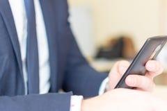 Mężczyzny obsiadanie podczas gdy używać mobilnego smartphone Ufny przedsiębiorca pracuje na telefonie fotografia stock