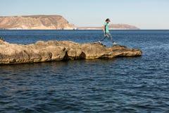 Mężczyzny odprowadzenie Na Rockowej formacji Przeciw morzu zdjęcia royalty free