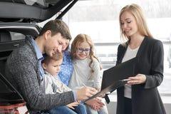 Mężczyzny podpisywania dokument samochodu zakup, szczęśliwa rodzina zdjęcie royalty free