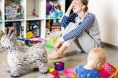 Męczący codzienny gospodarstwo domowe matki obsiadanie na podłodze z rękami na twarzy Dzieciak bawić się w upaćkanym pokoju Scate zdjęcie stock