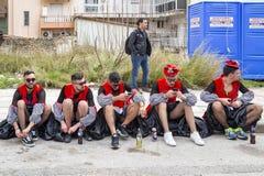 Męscy karnawałowej parady uczestnicy ubierający jako kobiety siedzą na chodniczku w Xanthi, Northeastern Grecja fotografia stock