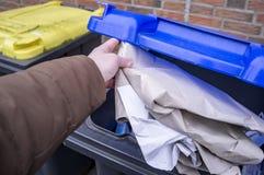 Męska ręka rzuca starego papier w kubła na śmieci z błękitnym deklem target1590_0_ odpady Pojęcie oszczędzanie postawa środowisko obraz royalty free