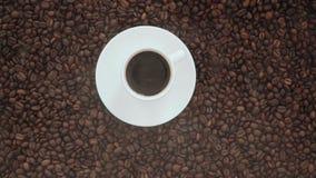 Męska ręka stawia filiżanka kawy z dymem na dużym stosie kawowe fasole zbiory