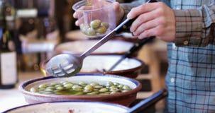 Męski klient W Garmażeryjnym plombowanie garnku Z Zielonymi oliwkami zbiory wideo