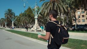 Męski podróżnik spaceruje samotnie na miasto ulicie, przegląda papierową mapę zbiory wideo