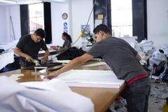 Męski pracownik na manufaktury falcowania szwalnych tkaninach i używać elektryczną tnącą tkaniny maszynę z łańcuszkową rękawiczką obraz royalty free