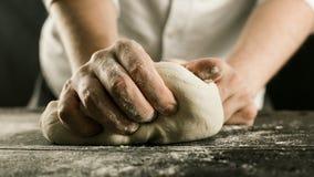 Męskie szef kuchni ręki ugniatają ciasto z mąką na kuchennym stole zdjęcie royalty free