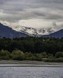 Mächtige Berge, die aus dem schönen See heraus haften Stockbild