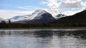 Mächtiger überschwemmter Flussstrom in Nord-Norwegen mit Wald und schneebedecktem Gebirgshintergrund stock video footage