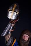 Mächtiger Ritter, der einen Sturzhelm anhält Lizenzfreie Stockfotos