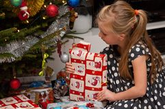 Mädchenöffnung Weihnachtsgeschenk unter Weihnachtsbaum Stockbilder